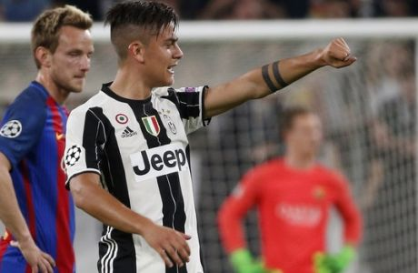 Juventus's Paulo Dybala celebrates after scoring his side's second goal during a Champions League, quarterfinal, first-leg soccer match between Juventus and Barcelona, at the Juventus Stadium in Turin, Italy, Tuesday, April 11, 2017. (AP Photo/Antonio Calanni)
