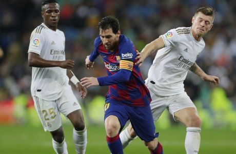 Barcelona's Lionel Messi, center, competes for the ball with Real Madrid's Toni Kroos, right, and Vinicius Junior during the Spanish La Liga soccer match between Real Madrid and Barcelona at the Santiago Bernabeu stadium in Madrid, Spain, Sunday, March 1, 2020. (AP Photo/Manu Fernandez)
