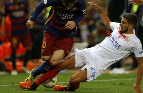 Barcelona's Lionel Messi is tackled by Sevillas Daniel Carrico during the final of the Copa del Rey soccer match between FC Barcelona and Sevilla FC at the Vicente Calderon stadium in Madrid, Sunday, May 22, 2016. (AP Photo/Francisco Seco)