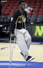 Virginia Commonwealth guard Briante Weber balances on crutches at midcourt during practice for an NCAA college basketball second-round game in Portland, Ore., Wednesday, March 18, 2015. VCU is to play Ohio State on Thursday. Weber is out with a right knee injury. (AP Photo/Don Ryan)