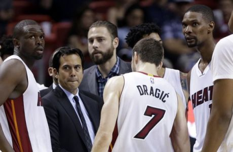 Miami Heat head coach Erik Spoelstra, third from left, talks with Luol Deng, second from left, Goran Dragic (7) and Chris Bosh, third from right, during the second half of an NBA basketball game against the New York Knicks, Wednesday, Jan. 6, 2016, in Miami. The Knicks defeated the Heat 98-90. (AP Photo/Lynne Sladky)