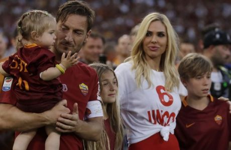 Roma's Francesco Totti holds her daughter Isabel, with the other daughter Chanel, his wife Ilary and his son Cristian walking next to him as he salutes his fans after an Italian Serie A soccer match between Roma and Genoa at the Olympic stadium in Rome, Sunday, May 28, 2017. Francesco Totti is playing his final match with Roma against Genoa after a 25-season career with his hometown club. (AP Photo/Alessandra Tarantino)
