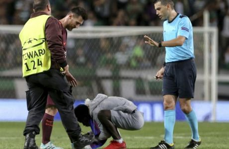 A fan who ran onto the pitch interrupting the match appears to try to kiss Barcelona's Lionel Messi, during a Champions League, Group D soccer match between Sporting CP and FC Barcelona at the Alvalade stadium in Lisbon, Wednesday Sept. 27, 2017. (AP Photo/Armando Franca)