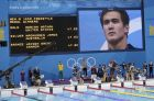 United States' gold medalist Nathan Adrian is seen on a large screen as he stands on the podium after his win in the men's 100-meter freestyle swimming final at the Aquatics Centre in the Olympic Park during the 2012 Summer Olympics in London, Wednesday, Aug. 1, 2012. (AP Photo/Lee Jin-man)