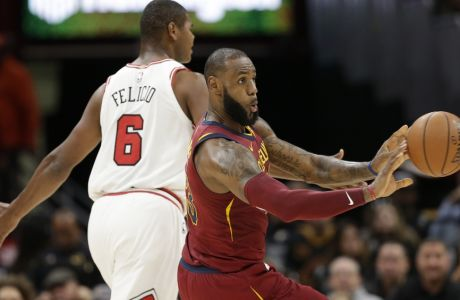 Cleveland Cavaliers' LeBron James, right, passes against Chicago Bulls' Cristiano Felicio (6), from Brazil, in the second half of an NBA basketball game, Tuesday, Oct. 24, 2017, in Cleveland. (AP Photo/Tony Dejak)