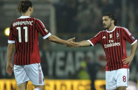 AC Milan's Gennaro Gattuso, right shakes hands with teammate Zlatan Ibrahimovic of Sweden at the end of a serie A soccer match between Parma and AC Milan at Parma Tardini stadium, Italy, Saturday, March 17, 2012. Milan won 2 - 0 to keep the lead of the Italian top league. (AP Photo/Marco Vasini)