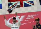 Mercedes driver Lewis Hamilton of Britain throws his trophy aloft as he celebrates after winning the Japanese Formula One Grand Prix at Suzuka, Japan, Sunday, Oct. 8, 2017. Third placed Red Bull driver Daniel Ricciardo of Australia looks on. (AP Photo/Eugene Hoshiko)