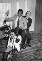 Riding on a Honda, Brazilian soccer king Pele flashes a V sign with Soichiro Honda, founder and advisor of the Honda Motor Company, during a press conference in Tokyo on Jan. 20, 1976. The 35-year-old New York Cosmos player came to Japan to sign a contract with the Japanese bike and automobile manufacturer to appear in Honda?s publicity films. (AP Photo/Keiichi Mori)