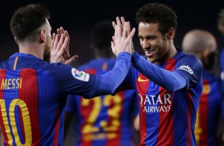 FC Barcelona's Lionel Messi, left, is greeted by team mate Neymar as they celebrate after scoring a goal during the Spanish La Liga soccer match between FC Barcelona and Valencia at the Camp Nou stadium in Barcelona, Spain, Sunday, March 19, 2017. (AP Photo/Manu Fernandez)