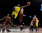 Michigan guard Zavier Simpson (3) drives to the basket between Loyola-Chicago's Donte Ingram, left, and Clayton Custer during the second half in the semifinals of the Final Four NCAA college basketball tournament, Saturday, March 31, 2018, in San Antonio. (AP Photo/David J. Phillip)