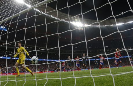 Atletico Madrid's Antoine Griezmann, right, celebrates after scoring a penalty kick past Chelsea goalkeeper Thibaut Courtois, left, during a Champions League group C soccer match between Atletico Madrid and Chelsea at the Wanda Metropolitano stadium in Madrid, Spain, Wednesday, Sept. 27, 2017. (AP Photo/Francisco Seco)