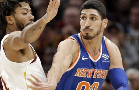 New York Knicks' Enes Kanter (00) passes against Cleveland Cavaliers' Derrick Rose (1) in the first half of an NBA basketball game, Sunday, Oct. 29, 2017, in Cleveland. (AP Photo/Tony Dejak)