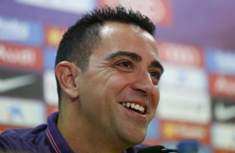 FC Barcelona's Xavi Hernandez smiles during a press conference at the Sports Center FC Barcelona Joan Gamper in San Joan Despi, Spain, Thursday, May 21, 2015. Barcelona midfielder Xavi Hernandez says he will leave the Catalan club after 17 trophy-laden seasons in which he set club records for appearances and titles won. The 35-year-old Xavi, who has played 764 matches for Barcelona, says he will cut his contract short by one year and leave after this season to go play for Qatari club Al-Sadd on a two-year contract. (AP Photo/Manu Fernandez)