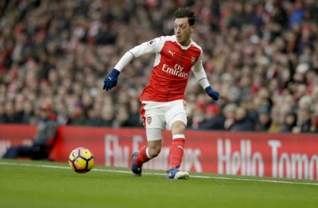 Arsenal's Mesut Ozil passes the ball during the English Premier League soccer match between Arsenal and Hull City at the Emirates Stadium in London, Saturday, Feb. 11, 2017. (AP Photo/Matt Dunham)