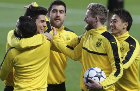 Dortmund's Andre Schuerrle, second right, jokes with teammate Marc Bartra, second left, during a training session at Benfica's Luz stadium in Lisbon, Monday, Feb. 13 2017. Borussia Dortmund will play Benfica Tuesday in a Champions League round of 16, first leg, soccer match. (AP Photo/Armando Franca)