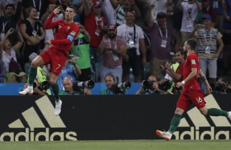 Portugal's Cristiano Ronaldo, left leaps as he celebrates after scoring his sides 1st goal form a penalty during the group B match between Portugal and Spain at the 2018 soccer World Cup in the Fisht Stadium in Sochi, Russia, Friday, June 15, 2018. (AP Photo/Manu Fernandez)