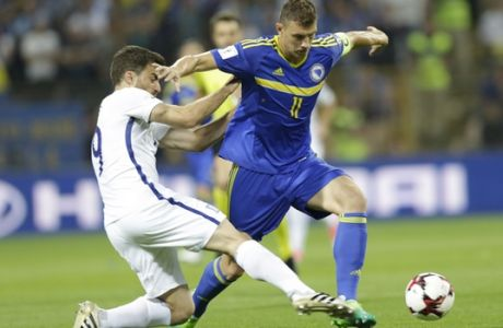 Bosnia's Edin Dzeko, right, duels for the ball with Greece's Sokratis Papastathopoulos, during their World Cup Group H qualifying match at the Bilino Polje Stadium in Zenica on Friday, June 9, 2017. (AP Photo/Amel Emric)