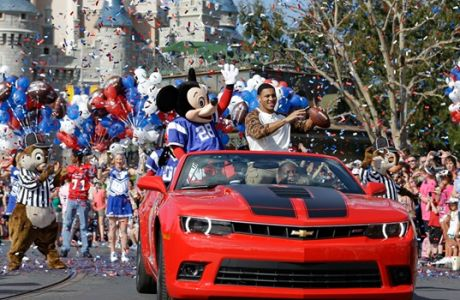 The 2014 Super Bowl MVP Malcolm Smith, a Seattle Seahawks linebacker, tosses a football as he rides in a parade at Walt Disney World with Mickey Mouse, Monday, Feb. 3, 2014, in Lake Buena Vista, Fla. The Seahawks defeated the Denver Broncos 43-8 in Sunday's Super Bowl XLVIII NFL football game in East Rutherford, N.J. (AP Photo/John Raoux)