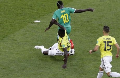Senegal's Sadio Mane, top, challenges for the ball with Colombia's Davinson Sanchez, bottom left, as Colombia's Mateus Uribe looks them during the group H match between Senegal and Colombia, at the 2018 soccer World Cup in the Samara Arena in Samara, Russia, Thursday, June 28, 2018. (AP Photo/Gregorio Borgia)