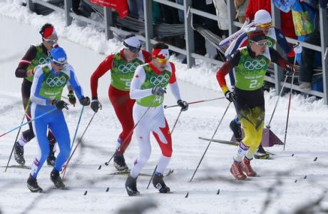 Austria's Max Hauke, Italy's Dietmar Noeckler, Switzerland's Gianluca Cologna, Canada's Alex Harvey, Germany's Tim Tscharnke and Norway's Petter Northug, from left, ski past spectators during a men's semifinal at the cross-country team sprint competitions at the 2014 Winter Olympics, Wednesday, Feb. 19, 2014, in Krasnaya Polyana, Russia. (AP Photo/Dmitry Lovetsky)