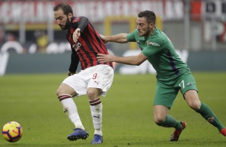 AC Milan's Gonzalo Higuain , left, challenges for the ball with Fiorentina's Jordan Veretout during a Serie A soccer match between AC Milan and Fiorentina, at the San Siro stadium in Milan, Italy, Saturday, Dec. 22, 2018. (AP Photo/Luca Bruno)
