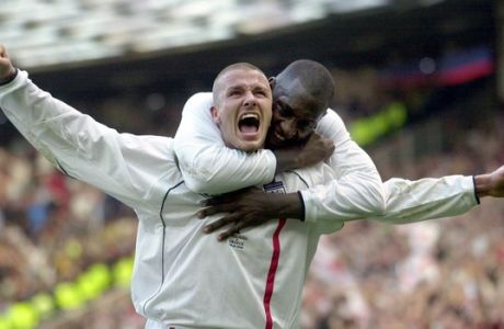 """FILE - This is a Saturday, Oct. 6, 2001 file photo of England's captain David Beckham, left, as he  is congratulated by teammate Emile Heskey after scoring their second goal against Greece during their 2002 World Cup qualifying match at Old Trafford Manchester England. David Beckham is retiring from soccer after the season, ending a career in which he become a global superstar since starting his career at Manchester United. The 38-year-old Englishman recently won a league title in a fourth country with Paris Saint-Germain. He said in a statement Thursday May 16, 2013 he is """"thankful to PSG for giving me the opportunity to continue but I feel now is the right time to finish my career, playing at the highest level.""""  (AP Photo/Adam Butler, File)"""