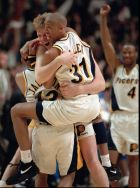 Indiana Pacers Reggie Miller (31) and Mark Jackson, left, hug Rik Smits after Smits hit the winning basket in the final second in game 4 of the NBA Eastern Conference Championship in Indianapolis May 29, 1995. (AP Photo/Michael Conroy)