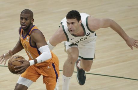 Phoenix Suns' Chris Paul drives to the basket past Milwaukee Bucks' Brook Lopez during the first half of Game 4 of basketball's NBA Finals Wednesday, July 14, 2021, in Milwaukee. (AP Photo/Aaron Gash)
