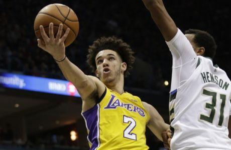 El jugador de los Lakers de Los Ángeles Lonzo Ball, izquierda, salta con el balón ante su rival de los Bucks de Milwaukee John Hensonm (derecha), durante la primera mitad del juego de la NBA que enfrentó a ambos equipos, el 11 de noviembre de 2017, en Milwaukee. (AP Foto/Darren Hauck)