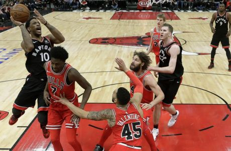 Toronto Raptors' DeMar DeRozan (10) shoots over Chicago Bulls' Justin Holiday (7) as Denzel Valentine (45) and Robin Lopez watch during the second half of an NBA basketball game Wednesday, Jan. 3, 2018, in Chicago. The Raptors won 124-115. (AP Photo/Charles Rex Arbogast)