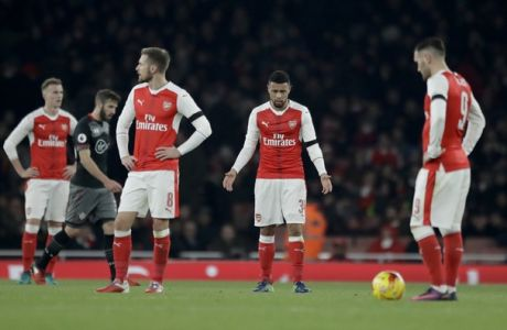 Arsenal's, from left, Aaron Ramsey, Francis Coquelin and Lucas Perez react as they wait to kick off after Southampton's Ryan Bertrand scored his team's second goal during the English League Cup quarterfinal soccer match between Arsenal and Southampton at the Emirates stadium in London, Wednesday, Nov. 30, 2016. (AP Photo/Matt Dunham)