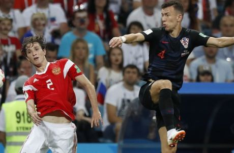 Russia's Mario Fernandes, left, and Croatia's Ivan Perisic jump for the ball during the quarterfinal match between Russia and Croatia at the 2018 soccer World Cup in the Fisht Stadium, in Sochi, Russia, Saturday, July 7, 2018. (AP Photo/Pavel Golovkin)