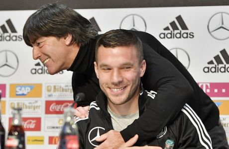 Germany's forward Lukas Podolski is embraced by national head coach Joachim Loew during a press conference prior the friendly soccer match between Germany and England in Dortmund, Germany, Tuesday, March 21, 2017. Podolski will play his last match for the national team against England on Wednesday. (AP Photo/Martin Meissner)