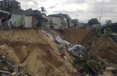 Residents stand at the edge of a sinkhole caused by recent rains in Natal, Brazil, Friday, June 20, 2014. The sinkhole swallowed cars and damaged the homes of some 150 families living in a poor neighborhood in the northern Brazilian city that's one of 12 hosting the World Cup matches. (AP Photo)