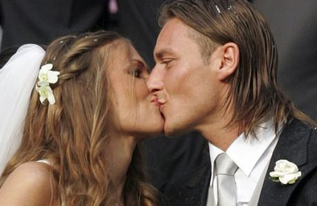 FILE - In this  June 19, 2005 file photo, Roma's captain Francesco Totti kisses his bride showgirl Ilary Blasi outside the Roman church of Santa Maria in Ara Coeli after their wedding. Totti celebrates his 40th birthday on Tuesday, Sept. 27, 2016,  but is showing no signs of slowing down and indeed seems to have found a new lease of life. He may not be Roma's 'Golden Boy' anymore but he is still very much 'the King of Rome.' (AP Photo/Plinio Lepri)