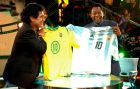 "epa000504717 A handout photo of Argentinean former soccer star, Diego Maradona (L), holding a Brazilian national soccer team jersey as his Brazilian counterpart, Pele, displays an Argentinian one during the new TV Show ""La Noche del Diez"" (the night of the ten), conducted by the Argentinean soccer player and transmitted on Monday night 15 August 2005 by ""Canal Trece"" (channel 13) in Argentina.  EPA/Canal Trece/HO"