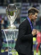 Atletico's head coach Diego Simeone walks past the trophy after the UEFA Super Cup final soccer match between Real Madrid and Atletico Madrid at the Lillekula Stadium in Tallinn, Estonia, Wednesday, Aug. 15, 2018. (AP Photo/Pavel Golovkin)