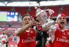 Arsenal's Mesut Ozil, left, celebrates with the trophy after winning the English FA Cup final soccer match between Arsenal and Chelsea at Wembley stadium in London, Saturday, May 27, 2017. Arsenal won 2-1. (AP Photo/Kirsty Wigglesworth)
