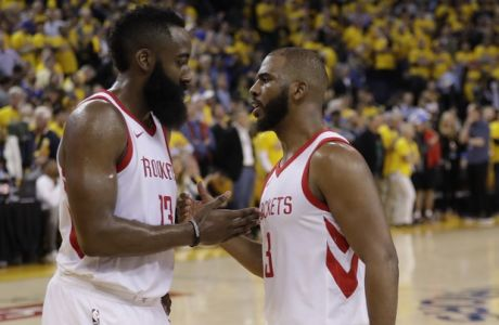Houston Rockets' Chris Paul, right ,shakes hands with teammate James Harden during the second half in Game 4 of the NBA basketball Western Conference Finals against the Golden State Warriors Tuesday, May 22, 2018, in Oakland, Calif. (AP Photo/Marcio Jose Sanchez)