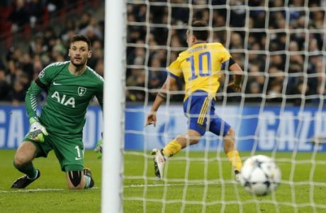 Tottenham goalkeeper Hugo Lloris watches the ball as Juventus' Paulo Dybala scores his side second goal during the Champions League, round of 16, second-leg soccer match between Juventus and Tottenham Hotspur, at the Wembley Stadium in London, Wednesday, March 7, 2018.(AP Photo/Frank Augstein))