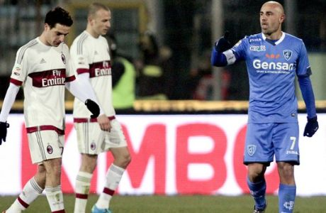 Empoli's Massimo Maccarone, right, celebrates after scoring the equalizing goal as AC Milan players walk in dejection, during a Serie A soccer match between Empoli and AC Milan, in Empoli, Italy, Saturday, Jan. 23, 2016. during a Serie A soccer match between Empoli and AC Milan, in Empoli, Italy, Saturday, Jan. 23, 2016. (AP Photo/Paolo Lazzeroni)