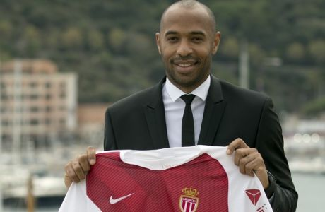 New AS Monaco head coach Thierry Henry holds up his club jersey during his official media presentation at the Monaco Yacht Club, Wednesday, Oct. 17, 2018. France's all-time leading scorer and an Arsenal great landed his first managerial job on Saturday after Monaco hired him as a replacement for Leonardo Jardim, who was dismissed this week. (AP Photo/Olivier Anrigo)