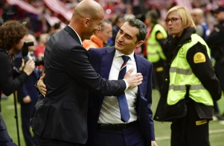 Real Madrid's head coach Zinedine Zidane, left, shakes hands with Athletic Bilbao's head manager Ernesto Valverde during the Spanish La Liga soccer match between Real Madrid and Athletic Bilbao, at San Mames stadium, in Bilbao, northern Spain, Saturday, March 18, 2017. Real Madrid won the match 2-1. (AP Photo/Alvaro Barrientos)
