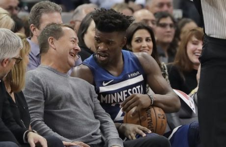 Minnesota Timberwolves guard Jimmy Butler (23) talks with a fan after he was fouled and fell into a seat during the second half of an NBA basketball game against the San Antonio Spurs, Wednesday, Oct. 17, 2018, in San Antonio. San Antonio won 112-108. (AP Photo/Eric Gay)