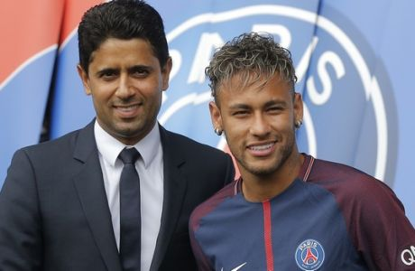 Brazilian soccer star Neymar shakes hands with the chairman of Paris Saint-Germain Nasser Al-Khelaifi following a press conference in Paris Friday, Aug. 4, 2017. Neymar arrived in Paris on Friday the day after he became the most expensive player in soccer history when completing his blockbuster transfer to Paris Saint-Germain from Barcelona for 222 million euros ($262 million).(AP Photo/Michel Euler)