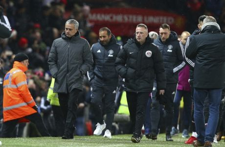 Manchester United coach Jose Mourinho, left, enters the field for the English Premier League soccer match between Manchester United and Manchester City at Old Trafford Stadium in Manchester, England, Sunday, Dec. 10, 2017. (AP Photo/Dave Thompson)