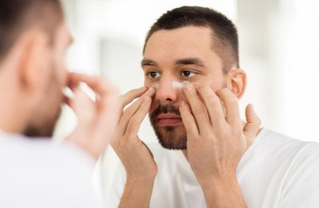 grooming, skin care and people concept - young man applying moisturizer to face and looking to mirror at home bathroom