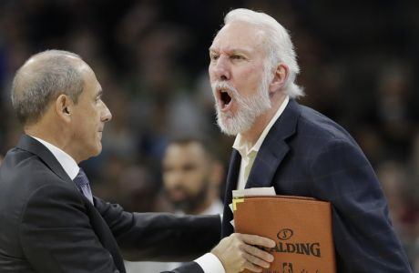 San Antonio Spurs head coach Gregg Popovich, right, is held back by assistant coach Ettore Messina, left, as he argues a call with an official during the first half of an NBA basketball game against the Dallas Mavericks, Monday, Nov. 27, 2017, in San Antonio. Popovich was ejected from the game. (AP Photo/Eric Gay)