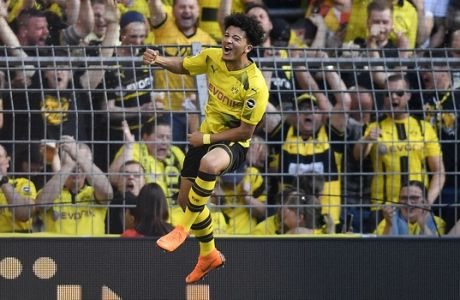 Dortmund's Jadon Sancho jumps for joy in front of the fans after he scored the opening goal against Leverkusen goalkeeper Ramazan Ozcan during the German Bundesliga soccer match between Borussia Dortmund and Bayer Leverkusen in Dortmund, Germany, Saturday, April 21, 2018. (AP Photo/Martin Meissner)