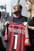 FILE - In this June 6, 2014 file photo, AC Milan president Silvio Berlusconi, left, holds a Milan shirt flanked by his daughter Barbara during a visit to the new team headquarter in Milan, Italy. The takeover of AC Milan has been completed Thursday, April 13, 2017, with Silvio Berlusconi selling the club to a Chinese consortium after 31 years in charge.  (AP Photo/Luca Bruno)